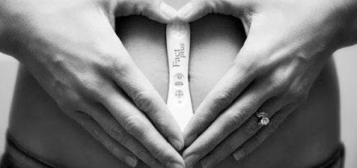 Mulher segurando teste de gravidez na frente da barriga, com as mãos formando um coração.
