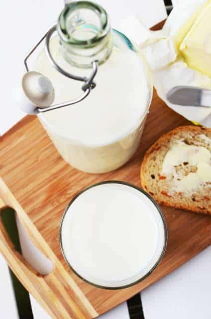 Jarra e copo de leite e fatia de pão.