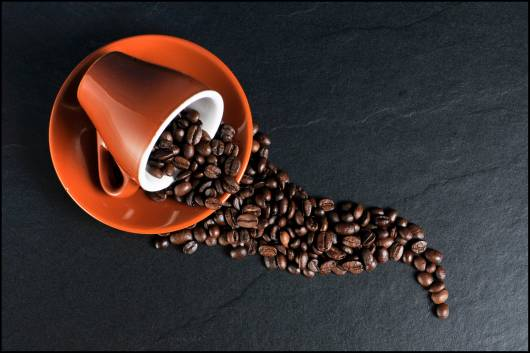 Xícara de café caída com grão de café.