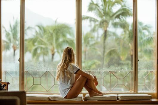 Mulher sentada perto de janela olhando para o lado de fora.