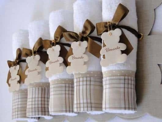 Rolinhos de toalhas com borda xadrez presas com lacinho marrom.