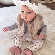 bebê com colete de pelo e laço na cabeça