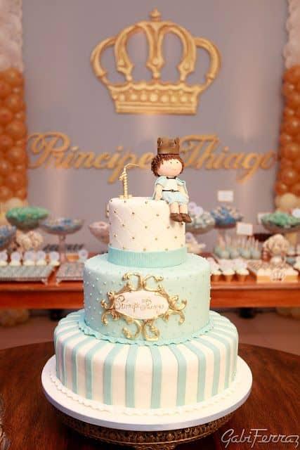 Bolo de três camadas azul e branco com príncipe sentado no topo.
