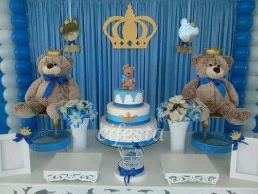 Mesa decorada com ursos grandes e painel do fundo com tecido azul e coroa.