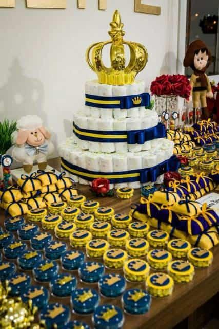 Mesa decorada com doces amarelos, azuis e bolo de fraldas.