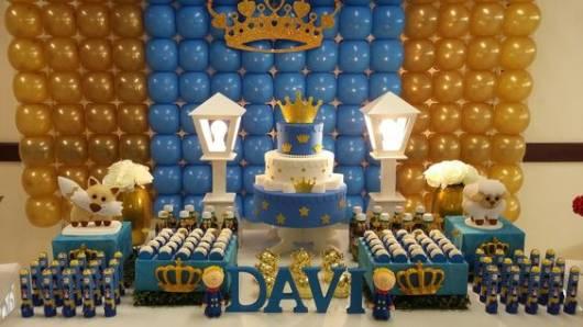 Mesa de bolo decorado com as cores azul, dourado e branco.