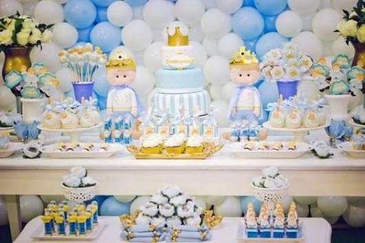 Imagem de mesa de bolo decorada com itens brancos e azuis.