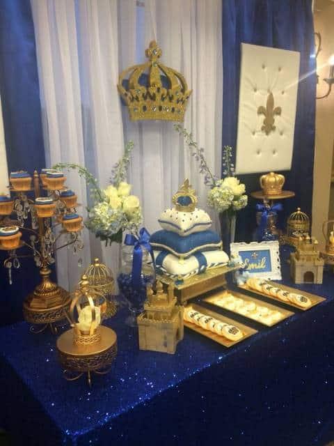 Mesa e painel decorados com azul marinho, e bolo que imita uma coroa sobre almofadas.