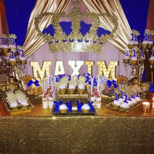 Festa decorada com painel azul marinho e toalha dourada.