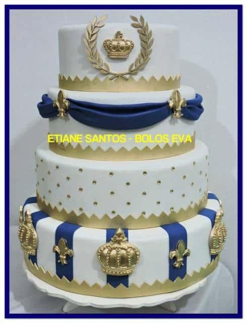 Bolo decorado de quatro camadas com as cores brancos, azul e dourado.