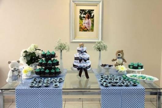 Mesa decorada com duas toalhas azuis, bolo de fraldas e ursinho.