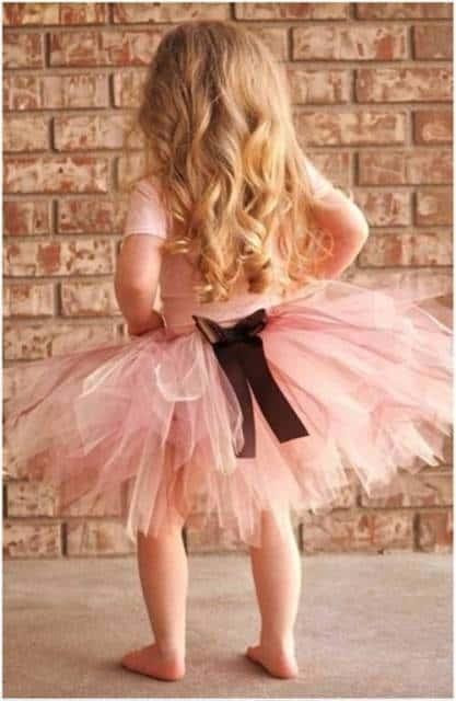 Menina descalça, com camiseta rosa e saia de tule com fita preta.
