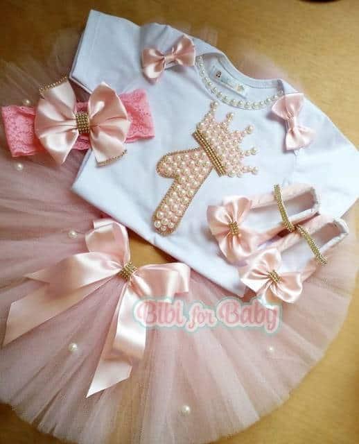 Camiseta branca com o número 1, saia rosa, acessório de cabelo e sapatilha.
