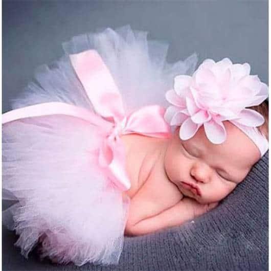 Bebê dormindo com saia rosa e acessório na cabeça.