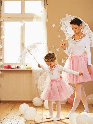 Mulher e criança usando saia rosa de tule e blusa branca de manga comprida.