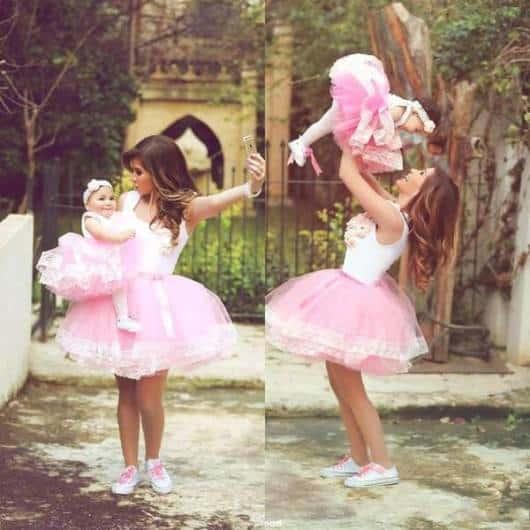 Mulher com sua filha no colo, ambas com saia rosa e blusinha branca.