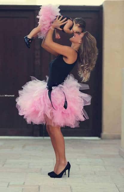 Mulher segurando sua bebê. Ambas usando regata preta e saia de tule rosa.