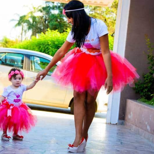 Mãe e filha usando saia de tule rosa choque e camiseta branca.