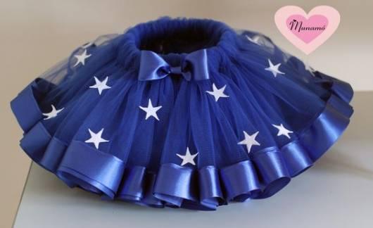 Saia de tule azul, barra com fita, laço e estrelas.
