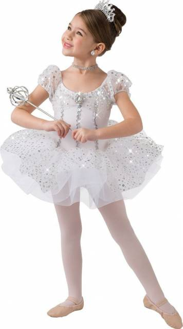 Menina com vestido branco, meia calça, sapatilha e porta coque.