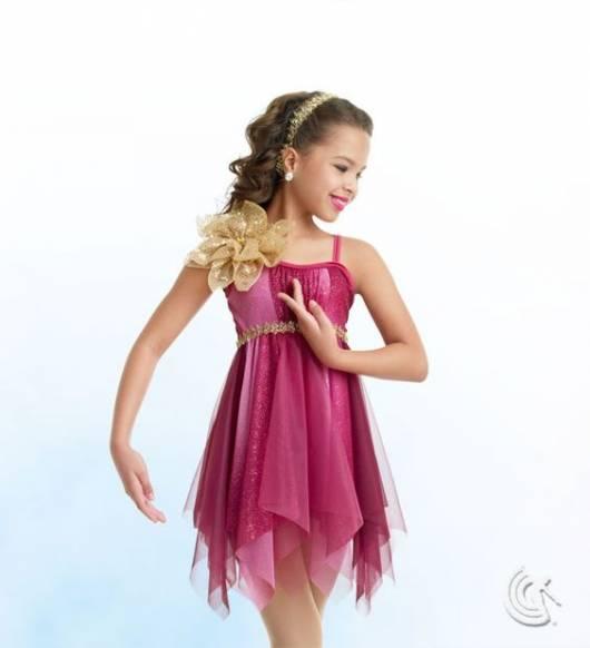 Menina usando vestido rosa com enfeite de flor no ombro.