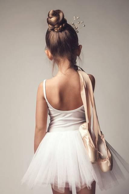 Menina de costas, com coque no cabelo, collant e saia brancas e sapatilha de balé no ombro.