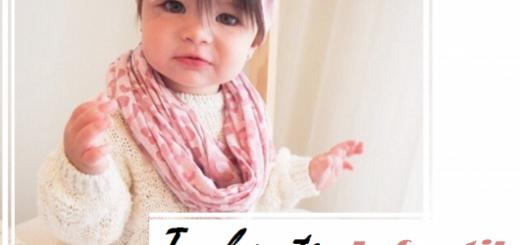 Criança veste body branco, gola cor de rosa e turbante no mesmo tom.