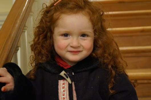 menina ruiva usando penteados para cabelo cacheado infantil