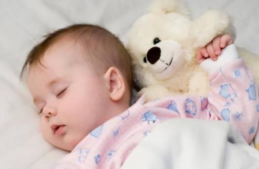 Bebê dormindo com bicho de pelúcia no berço