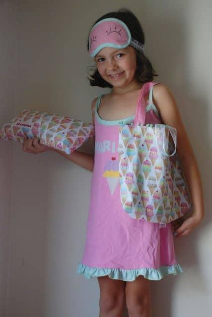 Menina com camisola, bolsa e travesseiro personalizados.