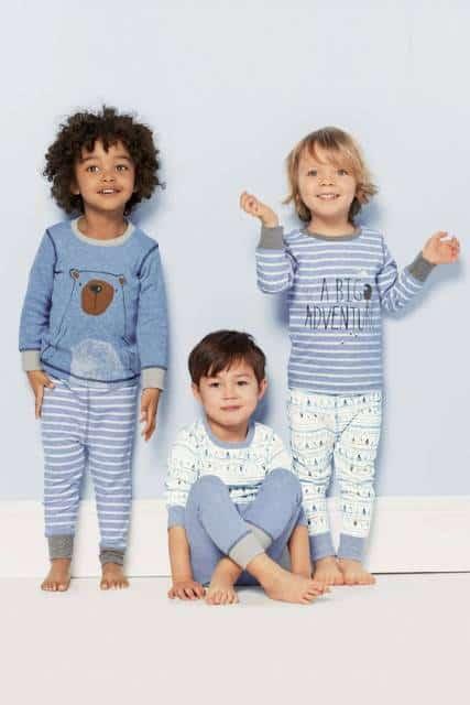 Meninos vestindo pijamas com estampas iguais.