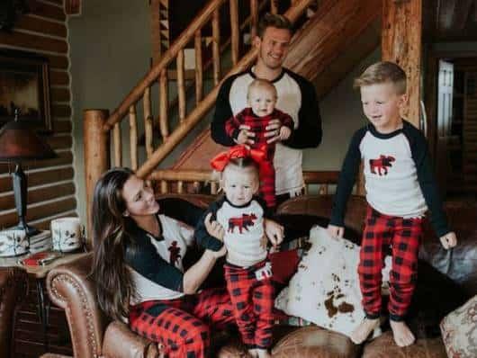 Pai, mãe e filhos com pijamas iguais.