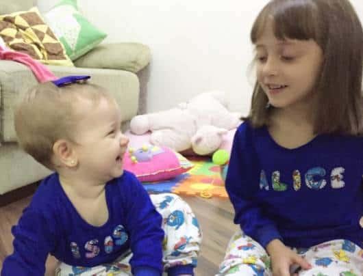 Menina e irmã bebê vestindo o mesmo pijama personalizado.