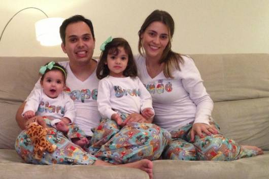 Mãe, pai e filhas com o mesmo pijama.