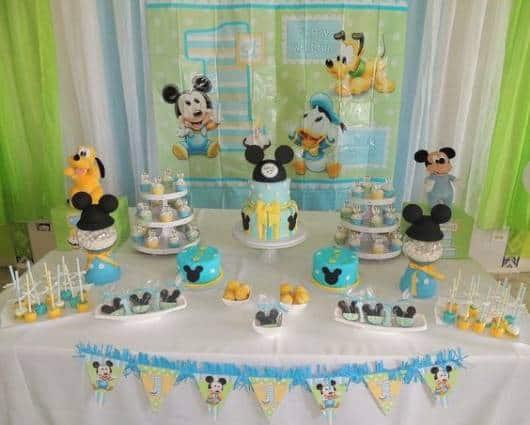 Mesa com bolo e docinhos do mickey.