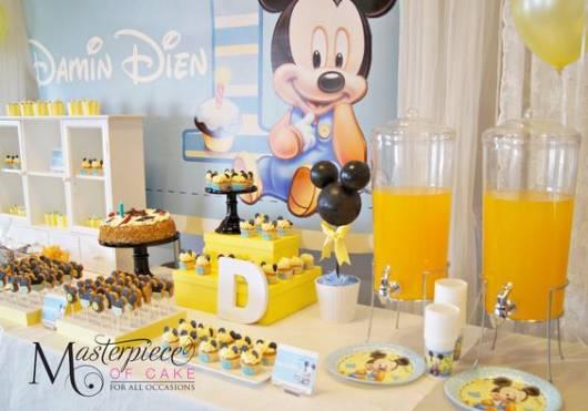 Mesa com painel do mickey baby e mesa com decoração dourada e amarela.