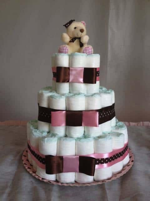 Bolo marrom e rosa com ursinho no topo.