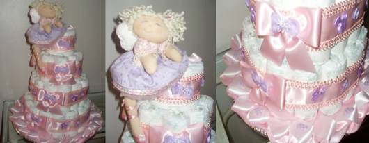 Bolo de fraldas com fitas e enfeite rosa e lilás.