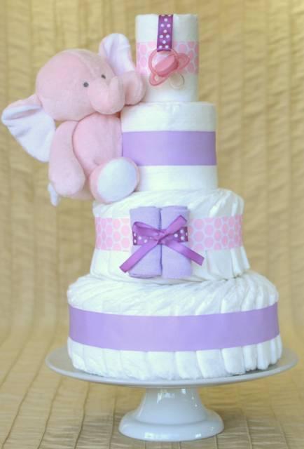 Bolo de fraldas branco com fitas e ursinho rosa e lilás.