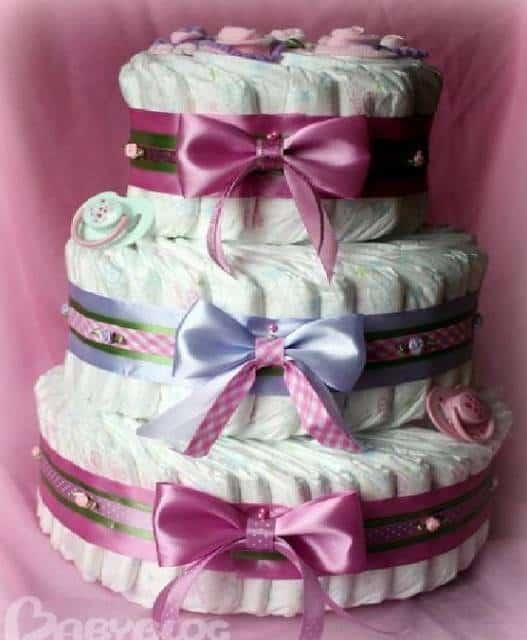 Bolo fake de fraldas com fitas rosa e lilás.