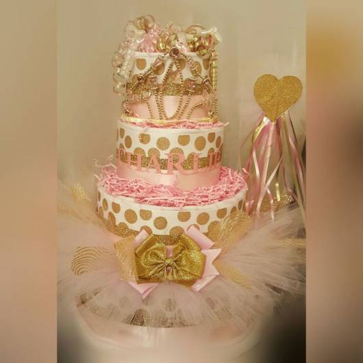 Bolo de fraldas dourado e rosa.
