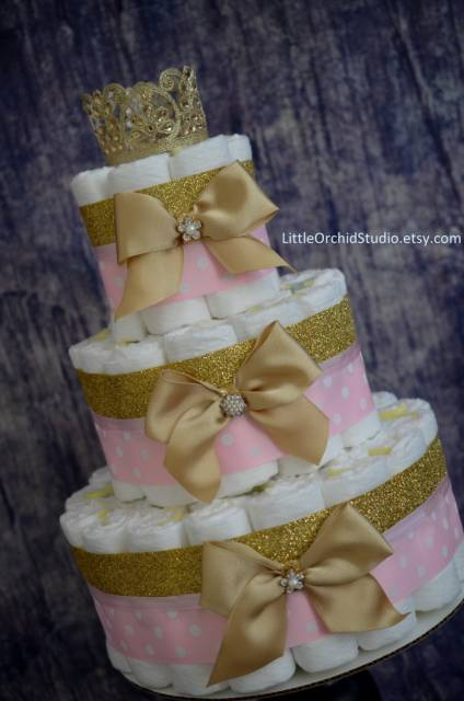 Bolo de fraldas em dourado e rosa.