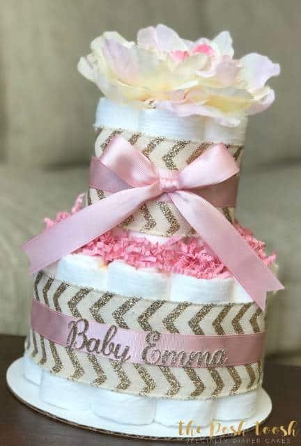 Bolo de fraldas com fitas rosas e douradas.