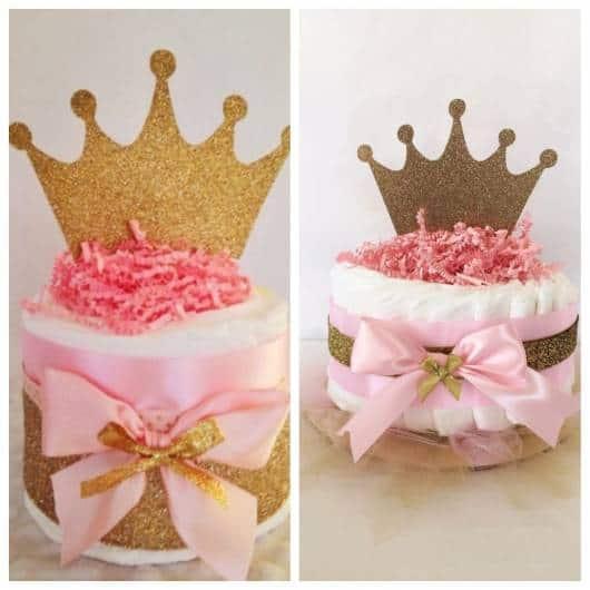Bolo de fraldas rosa e dourado com coroa no topo.