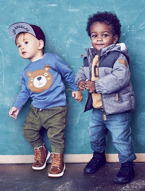 Dois meninos vestindo conjuntos de inverno.