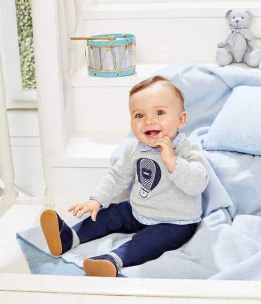 Bebê com moletom cinza e calça jeans.