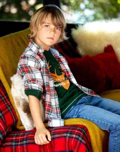 Menino com camisa xadrez, camiseta verde e calça jeans.
