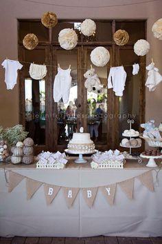 Mesa de chá de bebê com bodys pendurados acima.