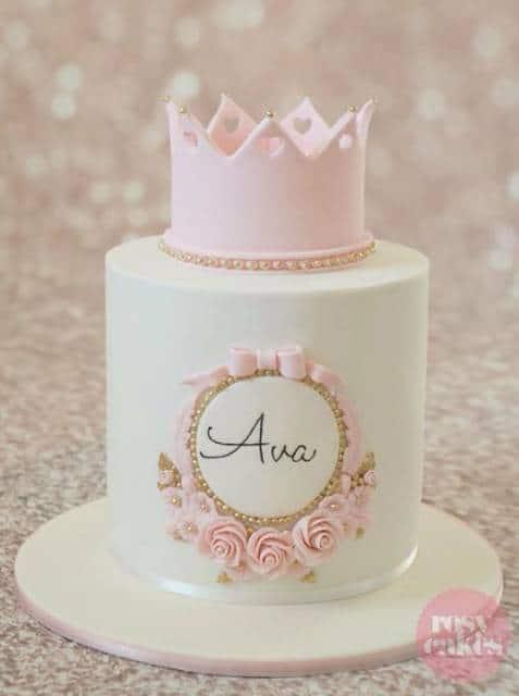 Bolo branco com coroa rosa no topo.