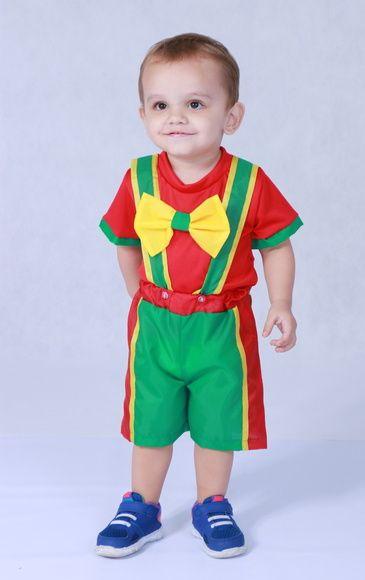 Menino vestido com roupa verde, vermelha e amarela.